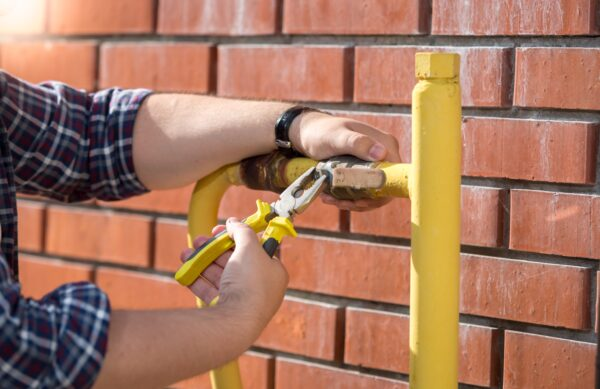 closeup-image-of-plumber-installing-new-valve-on-yellow-pipe-outside-of-house-min