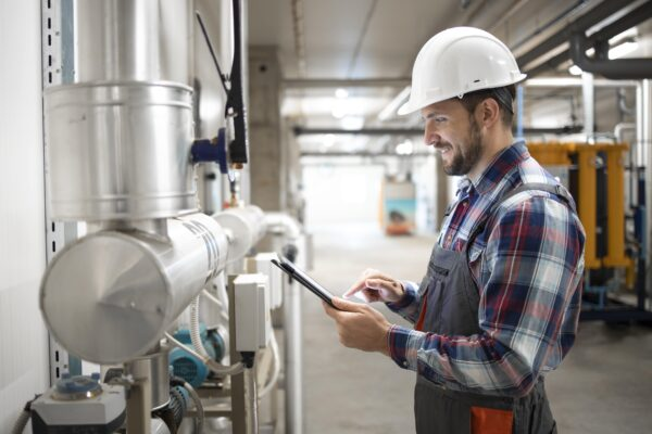 industrial-engineer-worker-holding-tablet-computer-and-setting-parameters-of-heating-system-in-factory-boiler-room-min